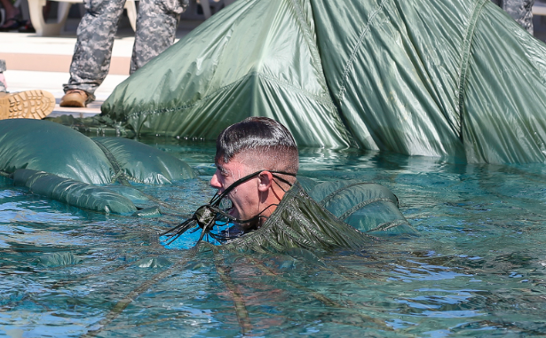 A member of 1/1st Special Forces Group swims out from underneath his parachute canopy in a pool in as part of water jump training. (photo Richard Rzepka - USAG Okinawa).