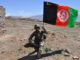 Afghan Soldier holds Afghan flag.